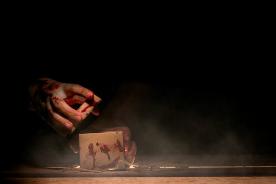 bloody hand holding and opening a box on wooden table in horror and mysterious concept