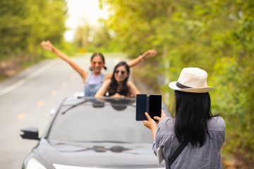 Traveler girls group enjoy taking photo with car on the road trip