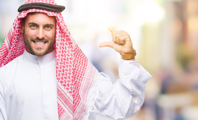Young handsome man wearing keffiyeh over isolated background smiling and confident gesturing with hand doing size sign with fingers while looking and the camera. Measure concept.