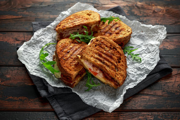 grilled sandwich with turkey, bacon, tomato and cheese on rustic wooden background