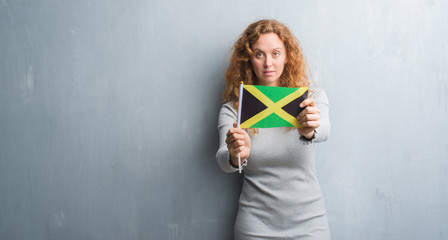 Young redhead woman over grey grunge wall holding flag of Jamaica with a confident expression on smart face thinking serious