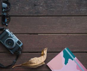 Autumn background on a wooden table with an old camera, autumn leaves and notepad.
