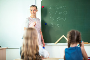 education, high school, university, teaching concept - group of schoolchild and teacher standing at white board at lecture