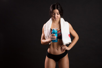 Sport. The sports young woman drinks protein cocktail in a shaker against black wall with copyspace. Sports nutrition concept.