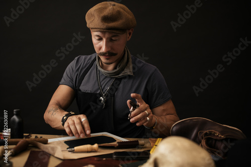 Leather craftsman working with natural leather  Shoemaker master at