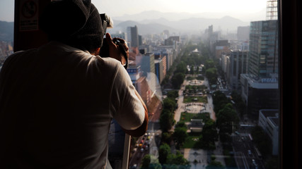 Silhouette image of man or tourist shotting photo at top of building.