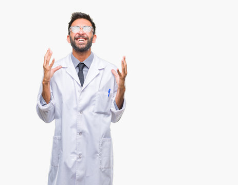 Adult hispanic scientist or doctor man wearing white coat over isolated background crazy and mad shouting and yelling with aggressive expression and arms raised. Frustration concept.