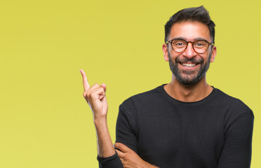 Adult hispanic man wearing glasses over isolated background with a big smile on face, pointing with hand and finger to the side looking at the camera. Wall mural
