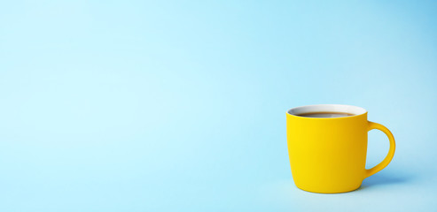 Yellow ceramic cup with hot aromatic coffee on color background