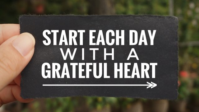 Motivational and inspirational quote - 'Start each day with a grateful heart' written on a paper. Vintage styled background.