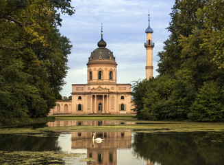 Schwetzingen Castle. Red mosque in the castle garden, in the foreground the lake with swan. Schwetzingen, Baden-Wuerttemberg, Germany, Europe