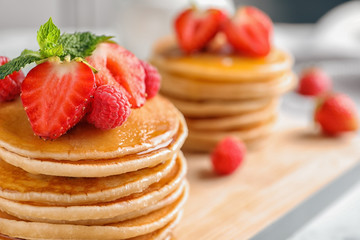 Tasty pancakes with berries and honey on wooden board, closeup