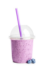 Tasty blueberry smoothie in plastic cup on white background