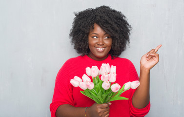 Young african american woman over grey grunge wall holding pink flowers bouquet very happy pointing with hand and finger to the side