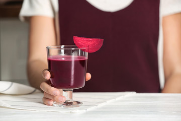 Woman with glass of beet smoothie at table, closeup
