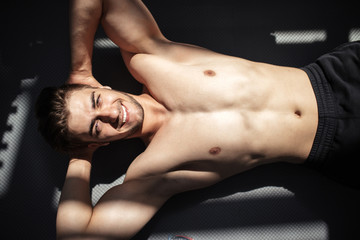 Attractive shirtless blond male bodybuilder rests lying on the floor indoors in dark gym, showing muscular torso and ripped abs