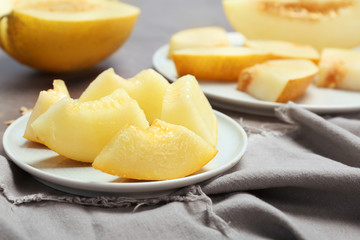 Plate with cut sweet melon on table