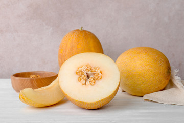 Fresh delicious sweet melons on table against color background