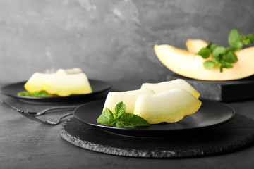 Slices of fresh ripe melon on table against gray background
