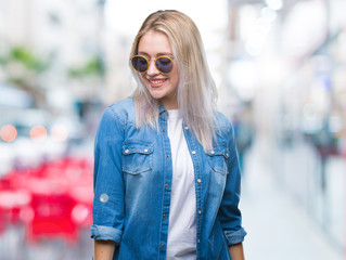 Young blonde woman wearing sunglasses over isolated background looking away to side with smile on face, natural expression. Laughing confident.