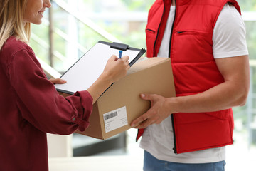 Young woman signing papers for delivered parcel indoors. Courier service