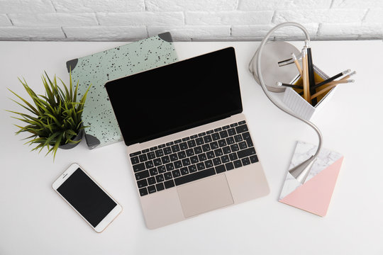 Modern workplace with laptop on table, above view. Mockup for design