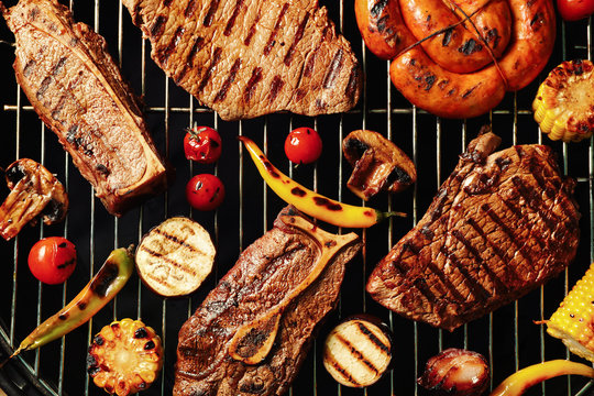 Fresh grilled meat steaks and vegetables on barbecue grate, top view
