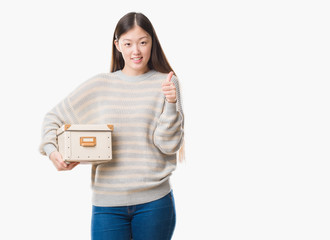 Young Chinese woman over isolated background holding a box happy with big smile doing ok sign, thumb up with fingers, excellent sign