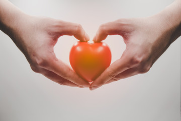 Red heart in hands on white background with light flare