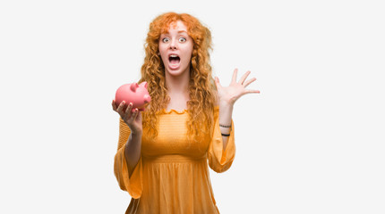 Young redhead woman holding piggy bank very happy and excited, winner expression celebrating victory screaming with big smile and raised hands