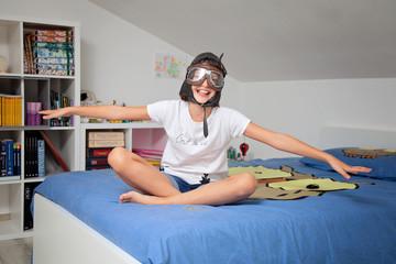bambina seduta sul letto sogna di volare
