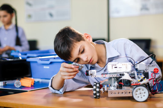 Little boy in robotics school makes robot managed from the constructor, child learns robot constructing.