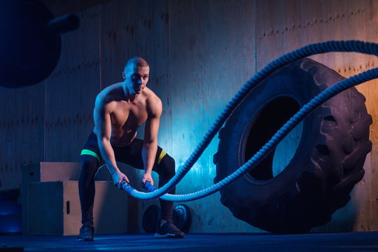 Man with battle ropes exercise in the fitness gym. Crossfit training workout.
