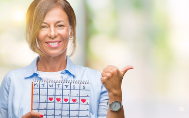 Middle age senior hispanic woman holding menstruation calendar over isolated background happy with big smile doing ok sign, thumb up with fingers, excellent sign