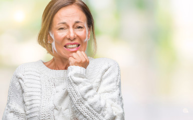 Middle age senior hispanic woman wearing winter sweater over isolated background looking stressed and nervous with hands on mouth biting nails. Anxiety problem.