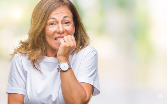 Middle age senior hispanic woman over isolated background looking stressed and nervous with hands on mouth biting nails. Anxiety problem.