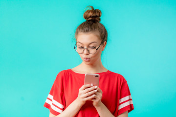 attractive hipster girl blowing kiss while taking photo, isolated blue background, free time, waste of time, girls like selfie
