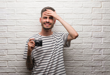 Young man holding vintage camera standing over white brick wall stressed with hand on head, shocked with shame and surprise face, angry and frustrated. Fear and upset for mistake.