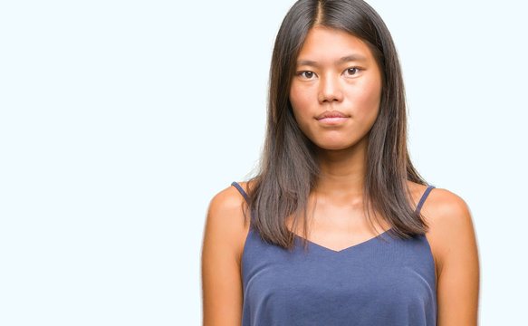 Young asian woman over isolated background with serious expression on face. Simple and natural looking at the camera.