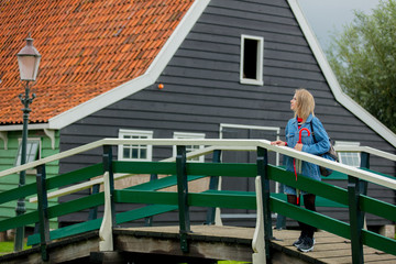Young girl in jeans jacket with umbrella stay on bridge near dutch house. Netherlands