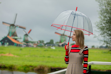 Young girl in dress with umbrella stay on bridge with dutch mills on background. Netherlands