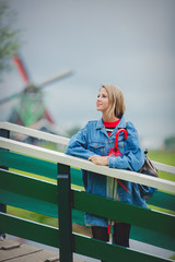 Young girl in jeans jacket with umbrella stay on bridge with dutch mills on background. Netherlands
