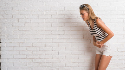 Young beautiful blonde woman over white brick wall with hand on stomach because indigestion, painful illness feeling unwell. Ache concept.