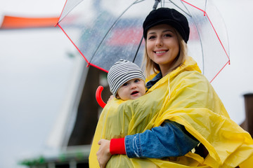 Young girl in rain suit with umbrella and a boby boy with dutch mills on background. Netherlands