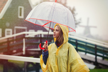 Young girl in rain suit with umbrella stay on bridge with dutch mills on background. Netherlands