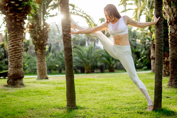 Young attractive woman practicing fitness, standing in stretching exercise, yoga pose, working out outdoors over nature background