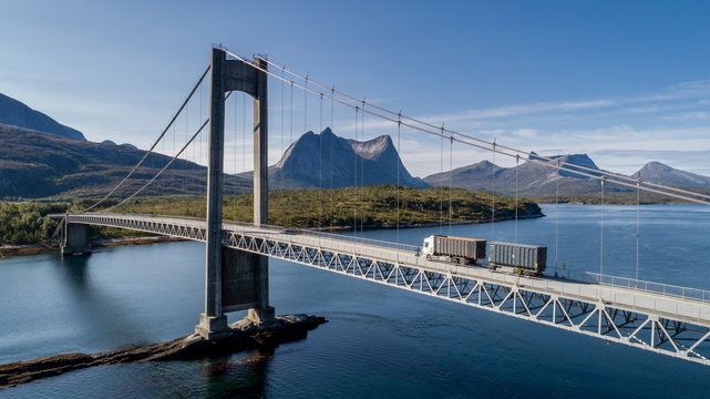 Aerial shot of a bridge over Efjord with a truck and mountain Stortinden in the background, Ballangen, Norway