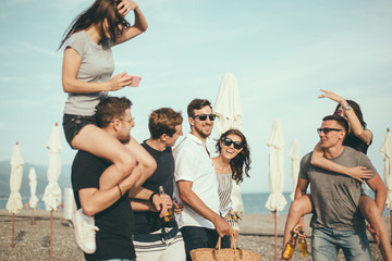 happy young men giving their girlfriends piggyback walks at beach. Group of friends enjoying beach