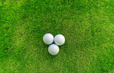 Three Golf Balls Lying on Green Grass View from Above