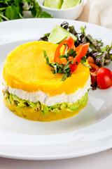 PERUVIAN FOOD. Causa rellena de pollo. Chicken causa rellena. Traditional peruvian dish from yellow potato, chicken, avocado on white plate